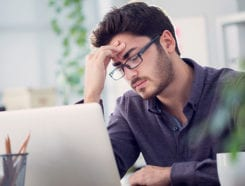 Man thinking while looking at laptop