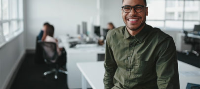 Man with glasses smiling while sitting on a desk in the office